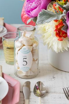 Simple idea for a beach-themed wedding. Just fill a jar with an assortment of seashells and the create a personalized labels with your table numbers.