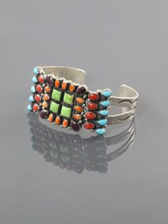 Cluster bracelet on hand stamped sterling silver split bracelet band. The center piece is set with four square gaspeite settings, and surrounded with orange and purple spiney oyster shell. The side pieces are set with red coral and turquoise.