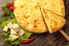 Ossetian Feta Cheese Pie. by Fisher-Photostudio. A colorful photo of traditional delicious beef osetinian pie. Traditional Ossetian feta cheese pie still life.