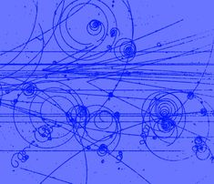 Particle tracks made visible with a bubble chamber immersed in a magnetic field.