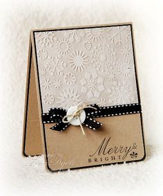 Snowflake embossing folder is used to create the upper half of this handmade Christmas card.  Simple kraft paper and black are the other accents, creating a clean and crisp look.