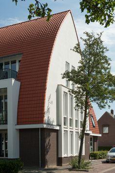 Toepassing van een spitsboogdak, met rode keramische dakpannen, past in een jarendertig architectuurstijl