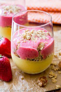 Para la primera capa necesitarás:- un plátano grande y congelado en rebanadas- una taza de mango en cachitos - 1/4 de taza de jugo de naranja. Mézclalo y ponlo en tu vaso.Para preparar la segunda capa necesitas: - un plátano grande- seis fresas rebanadas- 1/4 de yogurt griego de fresa - 1/4 de taza de leche.Una vez que esté listo ponlo encima del smoothie de mango en el vaso.Al final échale granola y disfruta.