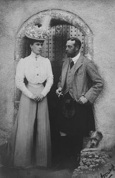 1906 Description: Photograph of the Prince and Princess of Wales, later King George V (1865-1936) and Queen Mary (1867-1953): standing outside door at Abergeldie. The Prince is dressed in Highland costume; his terrier dog, Happy, sits to right
