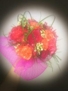 Caliente bridal bouquet; orange carnations, hot pink mini-carns, wax flower, bear grass, tree fern with a decomesh collar.