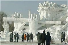 People gather in front of a snow-carved sculpture depicting a woman playing a flute