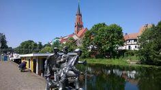 Die St. Marien-Andreas-Kirche mit dem Sportboothafen. Davor steht die Skulpturengruppe der Schleusensprucker. In den 1920er Jahren warteten Tagelöhner auf Arbeit im Hafen Rathenow. Sie vertreiben sich ihre Zeit oft mit Weitspuckwettspielen. Diesen Schleusenspukern hat der Rathenower Bildhauer Roth ein Denkmal gesetzt