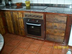 Armarios y cajonera  inferiores de cocina confeccionado con maderas recicladas y teñidos con productos naturales encima  del horno tiene rejilla para enfriamiento de este