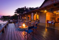 The main deck of the lodge at sunset. There is nothing better than sitting around the fire discussing stories of your activities that day and what wildlife you have seen. Outdoor Tables, Outdoor Decor, Lodges, How To Memorize Things, National Parks, Wildlife, Deck, Fire, Patio