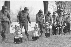After the liberation Feb '45 US soldiers escort traditionally dresses dutch children to a concert.