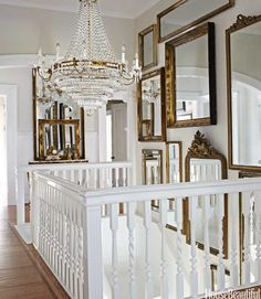 In the stair hall, daylight bounces off a Dutch chandelier and assorted mirrors.   - HouseBeautiful.com