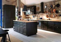 cocina modular de color negro con paredes de ladrillo