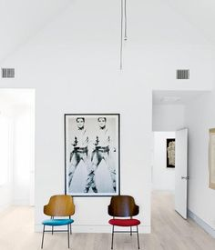 Minimalistic, very simple. all white, with contemporary wooden red and blue wooden chairs, and an elvis cowboy print.