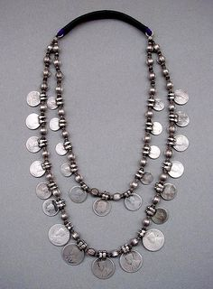 A two strand necklace from North India.The die-stamped pod-shaped beads have small wooden buffer beads in between to protect them from rubbing against each other. | Silver and wood |