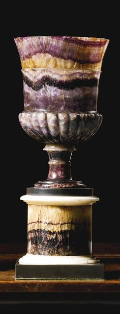 A George III Blue john vase circa 1800 with gadroon carving, on a turned socle and circular column with white marble ornament raised on a square black Ashford marble plinth 31cm. high, 12.5cm. diameter of top; 1ft. ¼in., 5in.