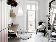 White bedroom with furry rug and workspace.