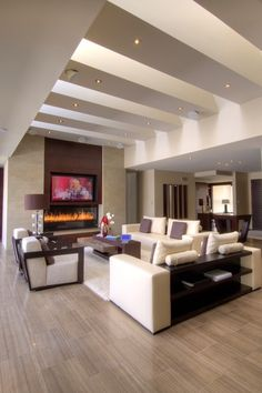 robert-dcosta: Home of the Year Award Winner A motorized panel lifts the wall out of view to reveal the 65 inch TV build in above the fireplace. Speakers are lowered from the ceiling at the same time. This photo shows the TV and speakers exposed. by London Audio Ltd (Home Media Design & Installation) || Robert D'Costa ||