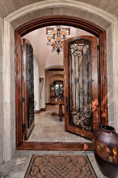 Old World accents at double-door entryway. Simple but elegant welcome mat, beautifully rich-tone oversized urn.