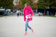 PARIS, FRANCE - SEPTEMBER 27: Alexandra Lapp wearing a fake fur jacket in pink from Jakke with a Faux Real statement on the back, red cashmere jumper by Heartbreaker with golden buttons, a long white blouse by Celine, Levis ReDone denim, Christian Louboutin heels in neon pink, sunglasses by Le Specs and a clutch by Yazburkey with a Dazzlin Smile application is seen during Paris Fashion Week Spring/Summer 2018 on September 27, 2017 in Paris, France. (Photo by Christian Vierig/Getty Images)