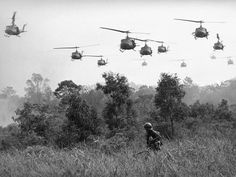 U.S. Army helicopters pour machine gun fire into the tree line to cover the advance of Vietnamese ground troops in an attack on a Viet Cong camp on March 29, 1965.