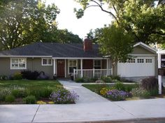 the curb appeal of this house with the paint colors and flowered yard is amazing