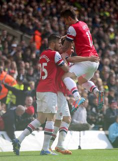 Aaron Ramsey Photos Photos - Aaron Ramsey of Arsenal celebrates scoring the opening goal with Carl Jenkinson and Olivier Giroud of Arsenal during the Barclays Premier League match between Norwich City and Arsenal at Carrow Road on May 11, 2014 in Norwich, England. - Norwich City v Arsenal - Premier League