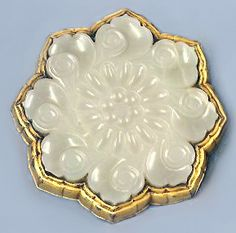 An 18th century Chinese eight-petalled white jade button mounted on gilt bronze, etched with flowers and scrolling foliage.