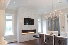 Modern marble slab dining room fireplace surround with inset TV above. Above Fireplace Ideas, Inset Fireplace, Marble Fireplace Surround, Fireplace Tv Wall, Dining Room Fireplace, Marble Fireplaces, Fireplace Remodel, Fireplace Surrounds, Modern Fireplaces