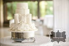 4 tier white wedding cake with lace petals and large fondant ribbon