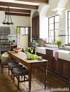 This kitchen's antique wooden table is paired with counter stools and farmhouse sinks.