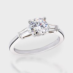 This popular high quality cubic zirconia ring features 1.0 carat brilliant round center with a single tapered baguette on each side. An approximate 1.40 total carat weight. This high quality cubic zirconia ring is set in solid 14K white gold, and is available in 14K yellow gold via Special Order.  Cubic zirconia weights refer to equivalent diamond carat size.
