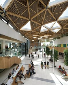 """Natural light pours in through triangular bays filled with EFTE rooflights by London-based Vector Foiltec, chosen because they are lighter than conventional double glazing. Each 48 square feet EFTE light consists of a three-layer cushion with a random printed frit pattern. Double-glazed windows cover the triangular openings in teaching and study areas to reduce rain noise. """"We originally envisioned more glass, but we ended up with half the number of light bays based on daylight modeling,""""…"""