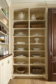 Amazing butler's pantry features floor to ceiling shelves filled with baskets and pottery adjacent to wall with stacked shelves over cream cabinets topped with butcher block.