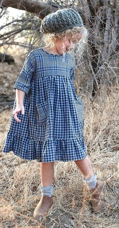 "Exclusive to our website is this adorable little blue check dress. It has two large pockets to put fun treasures in. The model is 49"" tall and is wearing a size 6. There is a one-inch grade between si"