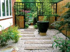 If you've been neglecting your side yard, try turning it into a low-maintenance entryway into your garden. In this space, bamboo rolls run vertically with black painted lattice, creating an effective Japanese theme in this private backyard garden. The gravel and wood pathway, with help from potted and easy-care plants, make this nook a breeze to maintain.