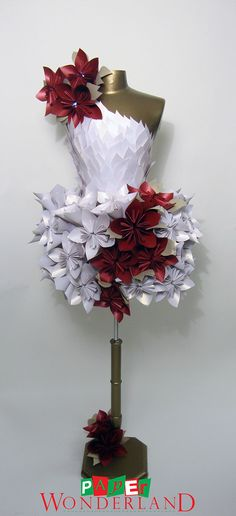 This paper dress was created for the cocktail/reception area at the 2010 PAVE Gala Dinner. The dress is made up of red, white and gold folded iridescent paper to resemble poinsettias. This design is exclusive of white LED's inside the red poinsettias atop…