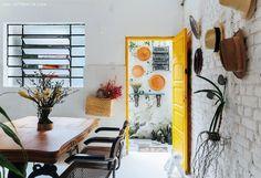 Cozinha com porta amarela, piso pintado com tinta epóxi e mesa antiga garimpada.