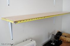 use old tape measure tape as trim on shelves - decorative and useful -