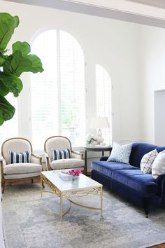 Blue velvet sofa with two white chairs and a grey rug