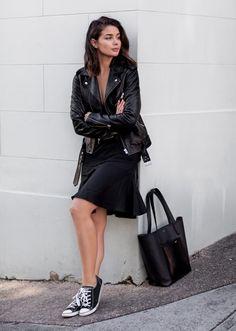 mujer con vestido negro y tenis converse