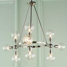 """Clean Polished Nickel lines join a sleek metal band that house the clear glass globes and create this Mid-Century mondern chandelier. Each cluster of lights can be rotated to create a new look and add just the right amount of glamour to your space. Slope ceiling adjustable.9x40 watts candle base T6 lamps max.(21.75""""Hx33.75""""W)60"""" OAH.Supplied with 36"""" of rods and 109"""" lead wire.5"""" round canopy."""