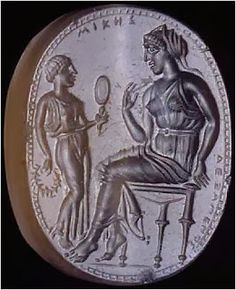 - figura femminile (Mikes) seduta su uno sgabello che riceve da una ancella una corona e uno specchio [FOTO];