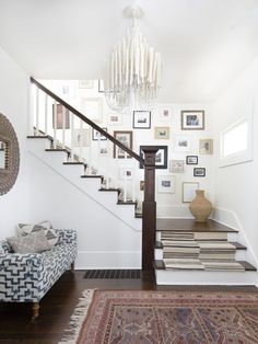 An entry way has a colorful Moroccan rug, a white chandelier with long ceramic tubes, and a striped runner on the stairs. Foyer Design, Staircase Design, House Design, Rustic Staircase, Staircase Ideas, Craftsman Cottage, Cottage Plan, White Chandelier, Modern Chandelier