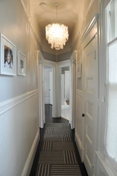 like: wainscotting with grey walls, capiz shell chandelier, dark wood floors and rug down the hall