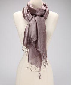 The smooth feel of this shimmering scarf adds a touch of finery to any outfit. Stand out as its luster reflects light and stay cozy in its soft, silky feel.