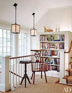 In a Hamptons home renovated by architect Andrew Pollock and furnished by Cullman & Kravis, a new stair landing created space for a reading nook. The elmwood comb-back Windsor chair dates from the 1780s, and the candlestick table is from the late 19th century. The sisal carpet and runner are from Beauvais.