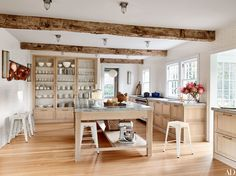 In the East Hampton house of publishing powerhouse Pilar Guzmán, bespoke Clayhaus Ceramics tile sheathes the kitchen, an inviting space anchored by a worktable and custom-made cabinetry; the ceiling lights are by Restoration Hardware. Sconces by Thomas O'Brien for Visual Comfort punctuate the walls.