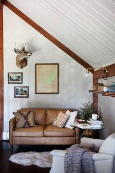 A leather love seat, sheepskin rug, wood trim, slanted shiplap ceiling, and mounted deer bust make for a cozy rustic living room corner.