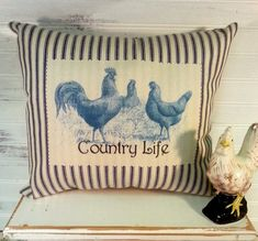 This French Farmhouse Country blue and white ticking rooster pillow features a vintage rooster and hen image in blue and the words Country Life. Ticking fabric is a staple in many country style homes and adds a cozy touch to a space. The vintage image has been printed onto cotton fabric and then adhered to the surface of the ticking fabric. I love working with vintage images and this pillow would be perfect in any French Country Farmhouse style home. Measures 11 tall X 13 wide Made from…