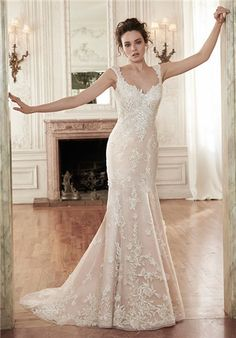 A stunning A-Line, this wedding gown features floral lace appliqués adorning an airy, tulle overlay. An unexpected plunging back adds a touch of drama. Finished with covered buttons over zipper closure.
